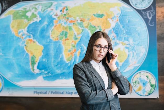 Junge geschäftsfrau, die telefonisch im büro spricht