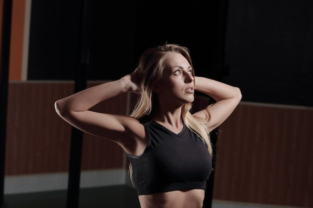 Junge geschäftsfrau, die übungen im fitnesscenter macht