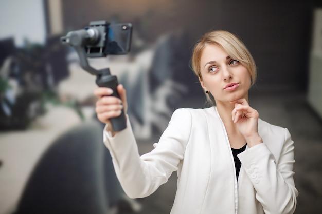 Junge geschäftsfrau, die videoblog auf smartphone im firmenbüro aufzeichnet.