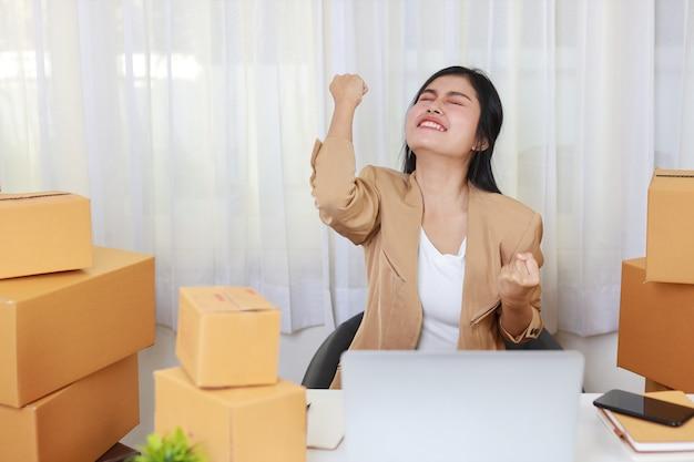 Junge geschäftsfrau, die von zu hause aus mit laptop-computer und online-einkaufsbestellung und kartonverpackung auf dem tisch arbeitet