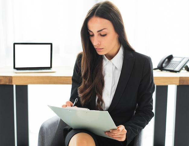 Junge geschäftsfrau, die vor schreibtischschreiben auf klemmbrett mit stift sitzt