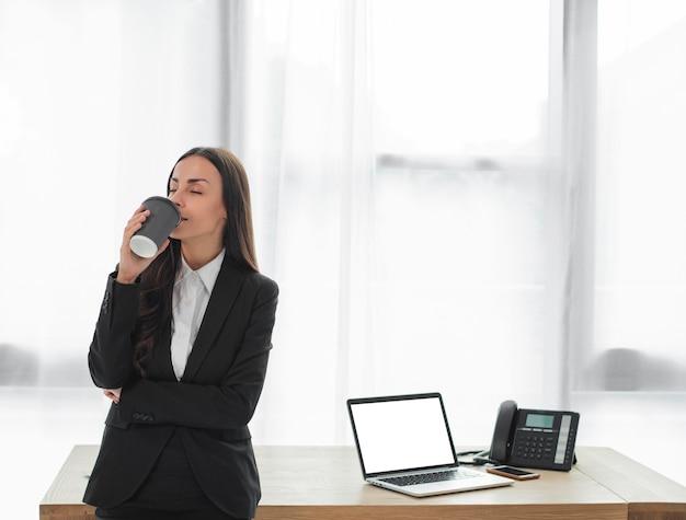 Junge geschäftsfrau, die vor trinkendem kaffee des schreibtisches von der wegwerfschale steht