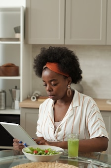 Junge geschäftsfrau, die während des frühstücks online-nachrichten durchschaut