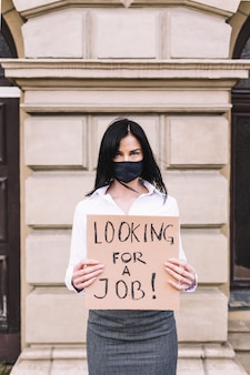 Junge geschäftsfrau, die zeichen hält, das einen job sucht, der schwarze gesichtsmaske trägt. arbeitslosigkeit nach koronavirus.