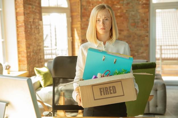 Junge geschäftsfrau gefeuert, sieht verärgert aus. muss ihre bürogegenstände packen und den arbeitsplatz für neue arbeiter verlassen. probleme in beruf, stress, arbeitslosigkeit, neuer lebensweise oder karriereende.