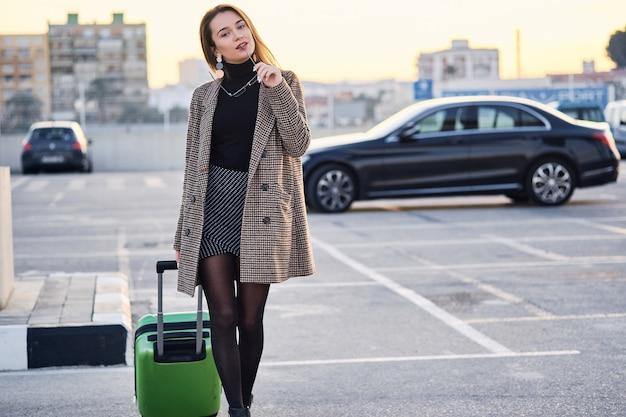Junge geschäftsfrau gegen schwarzes luxusauto