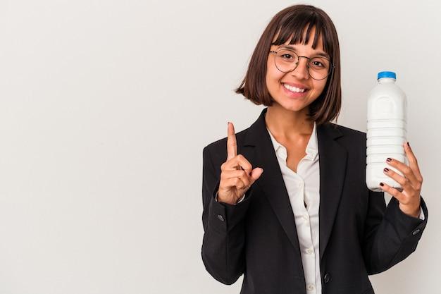 Junge geschäftsfrau gemischter abstammung, die eine milchflasche lokalisiert auf weißem hintergrund hält, der nummer eins mit dem finger zeigt.