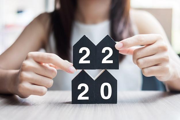 Junge geschäftsfrau hände halten 2022 frohes neues jahr mit hausmodell auf tischbüro. konzepte für neues haus, finanzen, sachversicherung, immobilien, sparen und neujahrsvorsätze