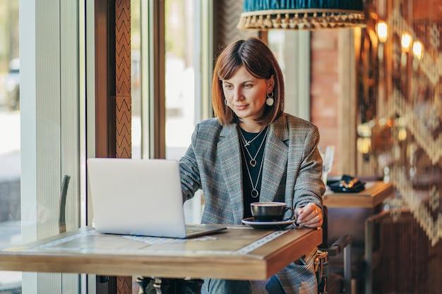Junge geschäftsfrau im grauen blazer, die am tisch im café sitzt und in notizbuch schreibt. freiberufler, der im café arbeitet. online-lernen.