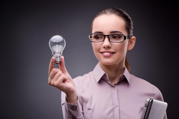 Junge geschäftsfrau im ideenkonzept mit glühlampe