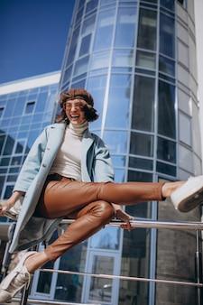 Junge geschäftsfrau im lässigen outfit durch das geschäftszentrum