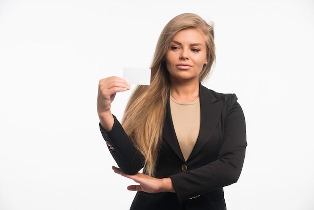Junge geschäftsfrau im schwarzen anzug, der visitenkarte des kunden prüft.