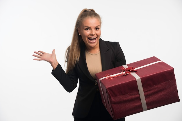 Junge geschäftsfrau im schwarzen anzug hält eine große geschenkbox und sieht fröhlich aus.