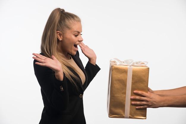 Junge geschäftsfrau im schwarzen anzug schaut auf eine geschenkbox und sieht überrascht aus.