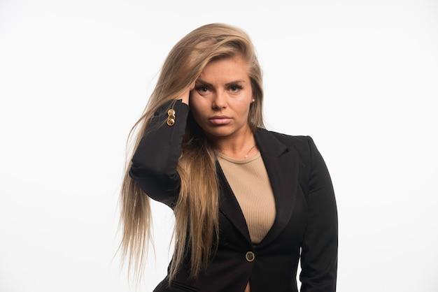 Junge geschäftsfrau im schwarzen anzug sieht ansprechend und verführerisch aus, während sie mit ihren haaren spielt.