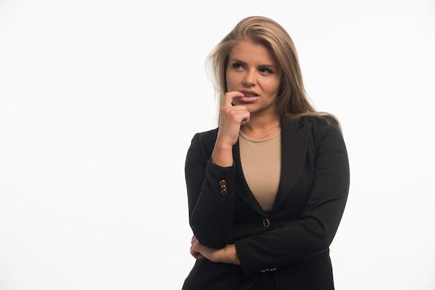Junge geschäftsfrau im schwarzen anzug sieht mit dem finger an ihrem mund verwirrt aus.