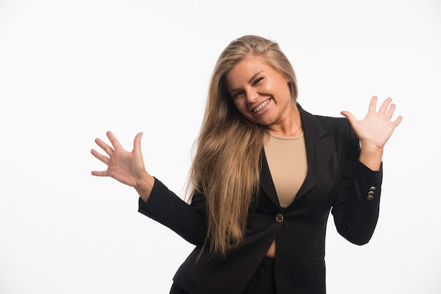 Junge geschäftsfrau im schwarzen anzug sieht positiv aus und benutzt handgesten.