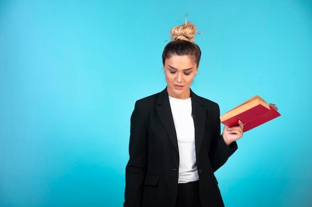 Junge geschäftsfrau im schwarzen blazer, der ein aufgabenbuch hält und die besprechungen überprüft