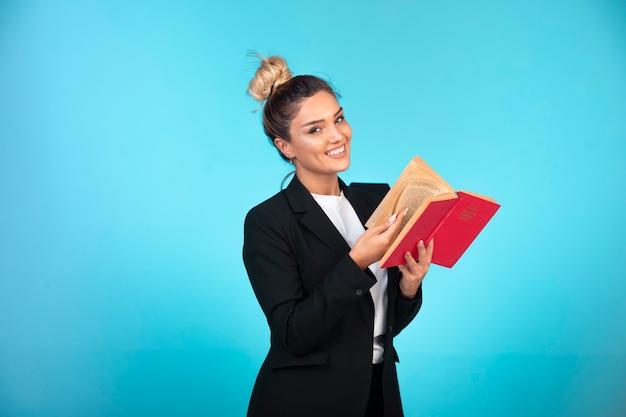 Junge geschäftsfrau im schwarzen blazer hält ein aufgabenbuch und fühlt sich positiv.
