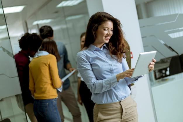 Junge geschäftsfrau im startbüro mit digitaler tablette vor ihren kollegen als teamleiter