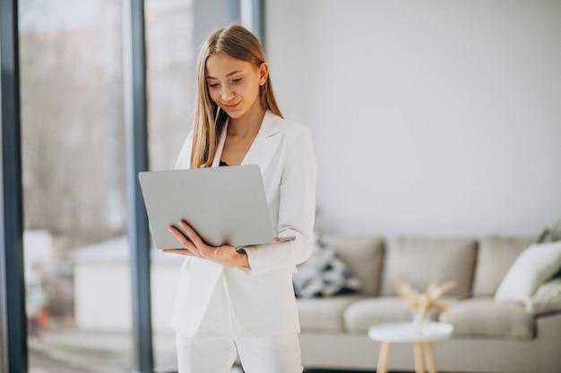 Junge geschäftsfrau im weißen anzug, der an einem computer arbeitet