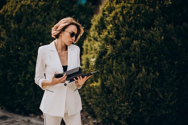 Junge geschäftsfrau im weißen anzug, der draußen am telefon spricht