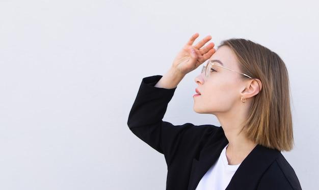 Junge geschäftsfrau in brille und einer schwarzen jacke schaut seitlich auf weiß