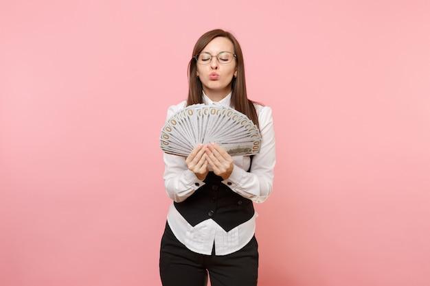 Junge geschäftsfrau in den gläsern, die bündel viele dollar halten, bargeld bläst lippenküssen einzeln auf rosa hintergrund. chefin. erfolgskonzept für karrierevermögen. kopieren sie platz für werbung.