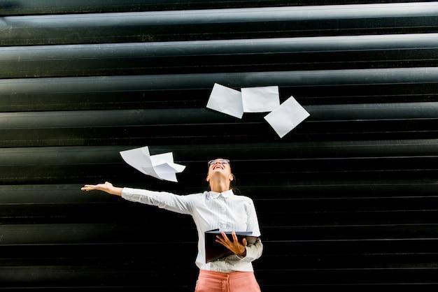 Junge geschäftsfrau in der geschäftskleidung papierdokumente im freien oben werfend