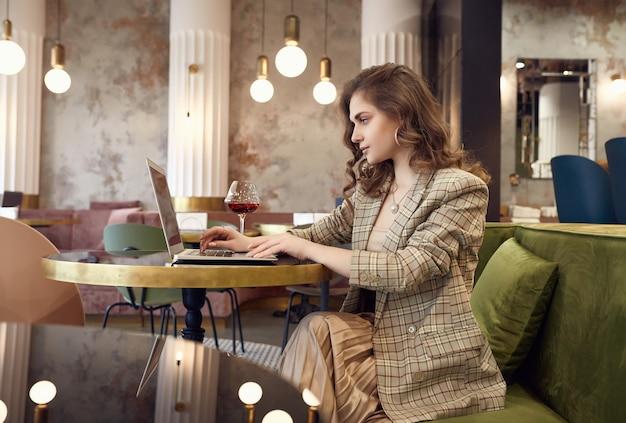 Junge geschäftsfrau in der intelligenten freizeitkleidung trinkt wein und arbeitet am laptop