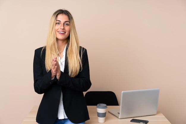 Junge geschäftsfrau in einem büro, das applaudiert