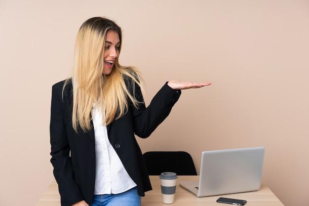 Junge geschäftsfrau in einem büro, das imaginären copyspace auf der handfläche hält