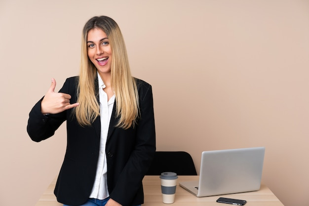 Junge geschäftsfrau in einem büro, das telefongeste macht