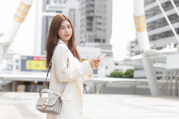 Junge geschäftsfrau in einem cremefarbenen anzug benutzt im freien ein mobiltelefon (smartphone), um mit partnern in kontakt zu treten, während sie im büro arbeitet.