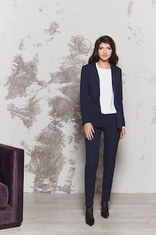 Junge geschäftsfrau in einem stylischen blauen anzug und weißer bluse geschäftsmodekonzept Premium Fotos