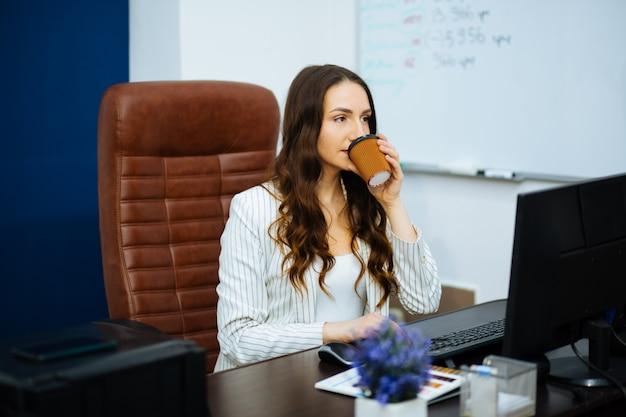 Junge geschäftsfrau in einer weißen jacke sitzt auf einem bürostuhl, der kaffee denkt und trinkt