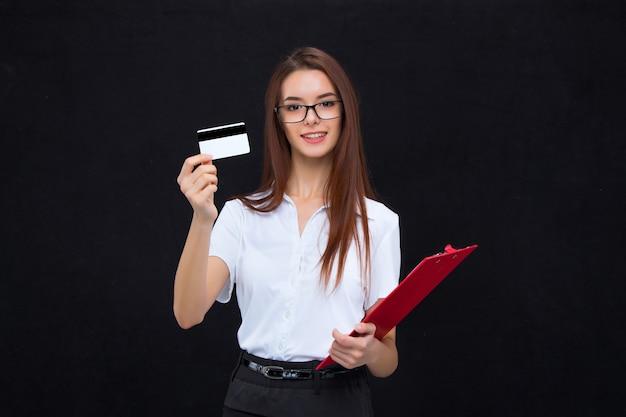 Junge geschäftsfrau in gläsern mit kreditkarte und zwischenablage für notizen
