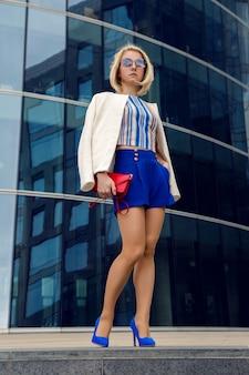 Junge geschäftsfrau in kurzen blauen stämmen, die stehen und auf ein treffen von der glasbank, hohes gebäude warten
