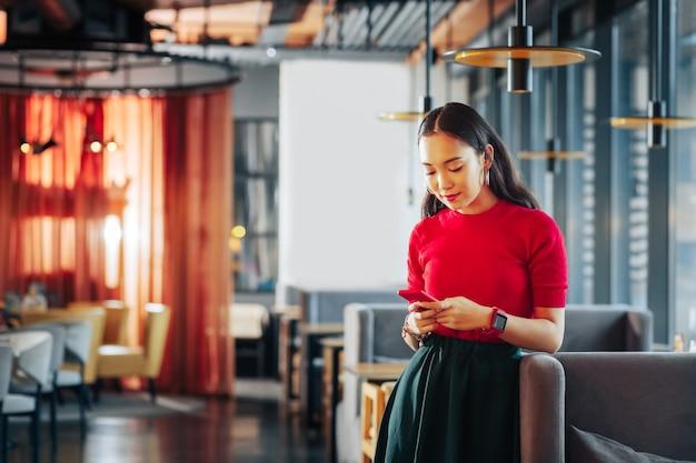 Junge geschäftsfrau junge geschäftsfrau, die ein restaurant besitzt, trägt einen dunklen rock und ein rotes hemd