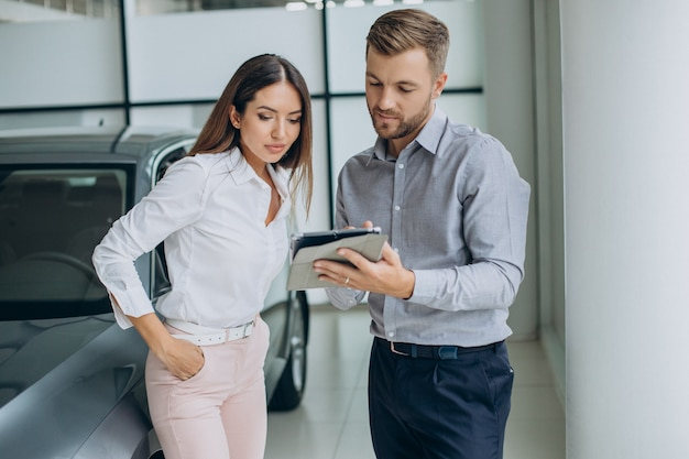 Junge geschäftsfrau kauft ein auto im autohaus