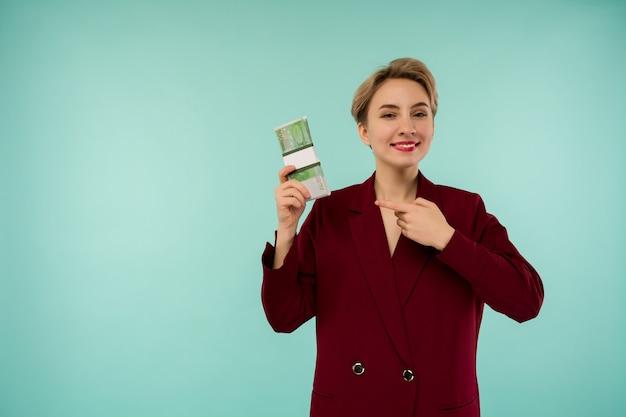 Junge geschäftsfrau lächelnd halten sich an einen stapel geld und zeigen mit dem finger auf bargeld