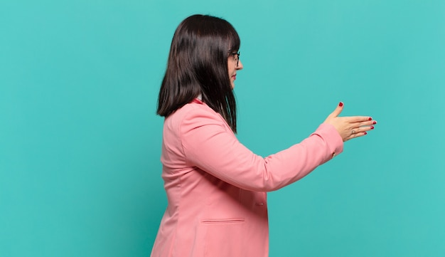 Junge geschäftsfrau lächelt, begrüßt sie und bietet einen handschlag an, um ein erfolgreiches geschäft abzuschließen, kooperationskonzept