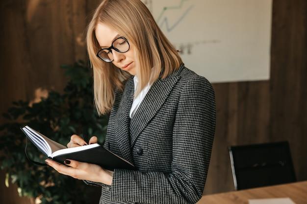Junge geschäftsfrau macht notizen in einem notizbuch im büro.