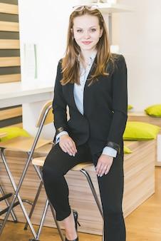 Junge geschäftsfrau mit brille sitzt auf einem stuhl, lächelt und schaut in die kamera