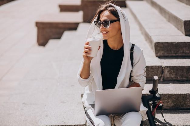Junge geschäftsfrau mit dem laptop, der auf treppen mit roller sitzt