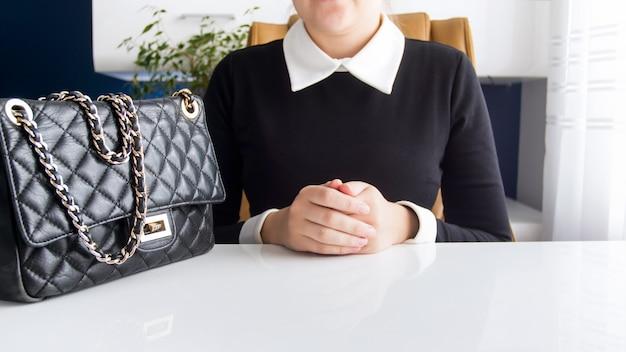 Junge geschäftsfrau mit dem schwarzen geldbeutel, der hinter weißem hölzernem schreibtisch im büro sitzt.