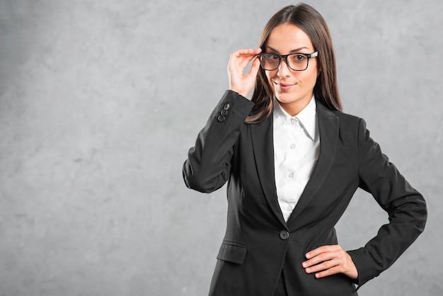 Junge geschäftsfrau mit den schwarzen brillen, die vor wand stehen