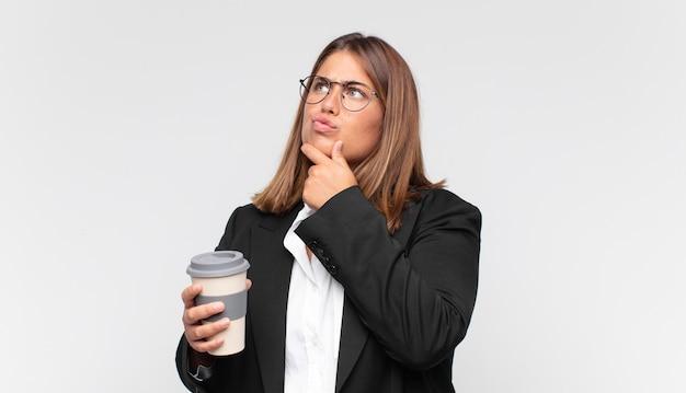 Junge geschäftsfrau mit einem kaffee, der nachdenkt, sich zweifelhaft und verwirrt fühlt, mit verschiedenen optionen und sich fragt, welche entscheidung sie treffen soll