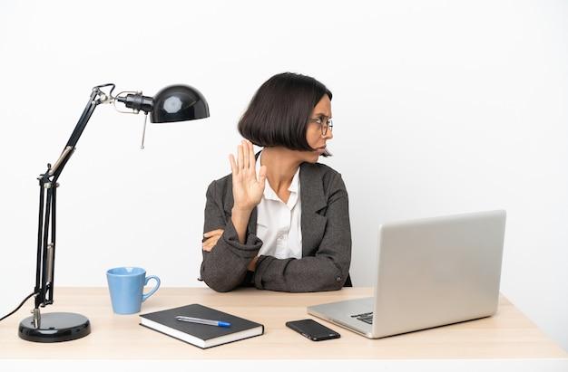Junge geschäftsfrau mit gemischter abstammung, die im büro arbeitet, stoppgeste macht und enttäuscht ist