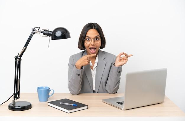 Junge geschäftsfrau mit gemischter abstammung, die im büro arbeitet, überrascht und zeigt seite